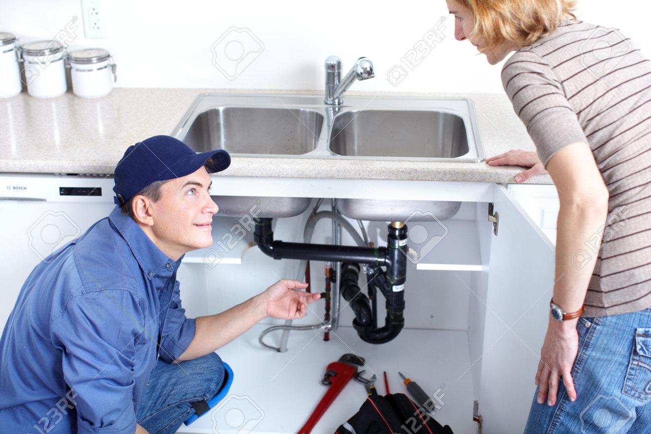 8255782 Mature plumber fixing a sink at kitchen Stock Photo plumbing plumber repair