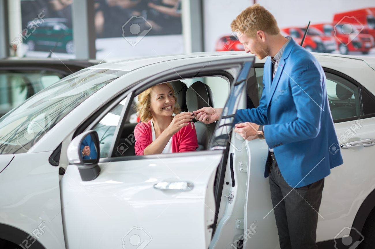 Buying A New Car Happy Woman Buying A New Car And Salesman Handling Keys