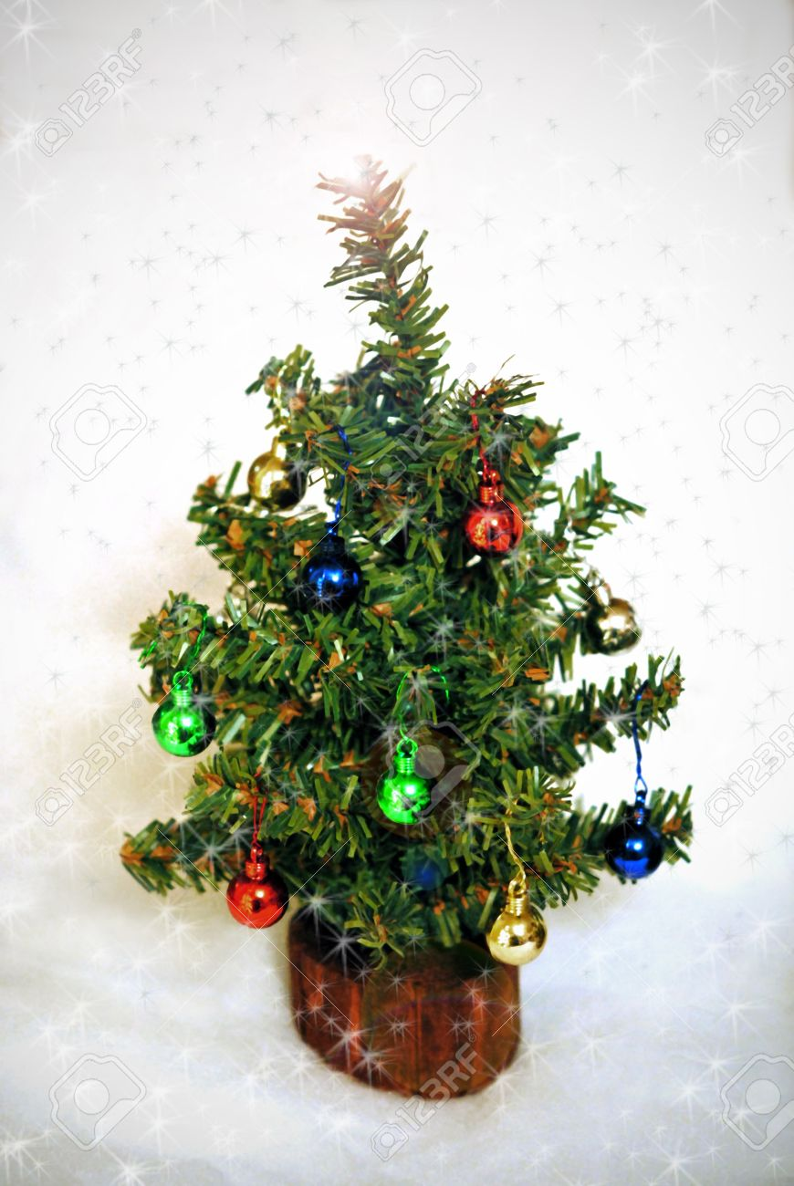 Miniature christmas tree with tiny ornaments amid falling snow stock photo 17034475