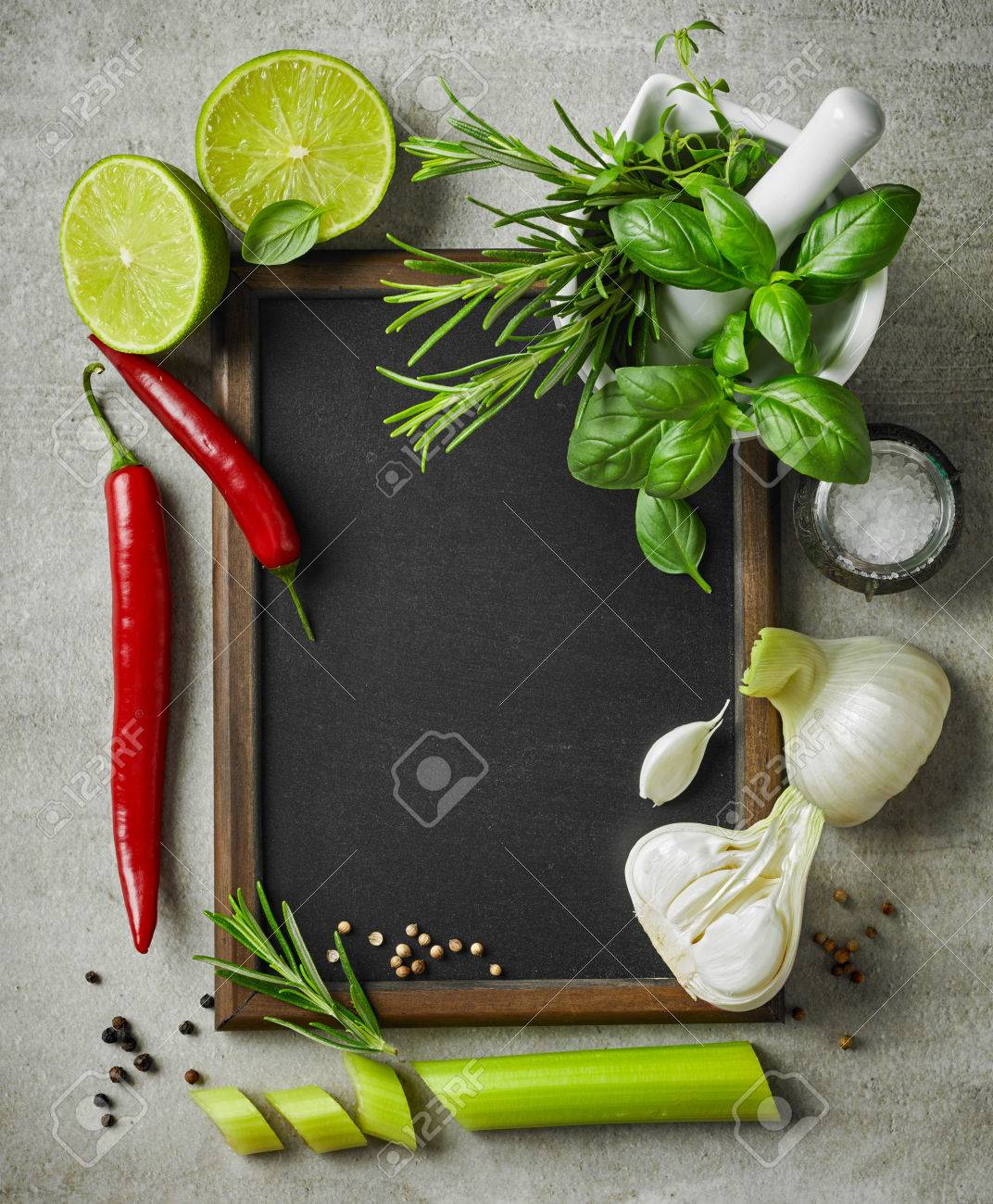 57923107 fresh herbs and spices and blackboard on gray kitchen table top view Stock Photo