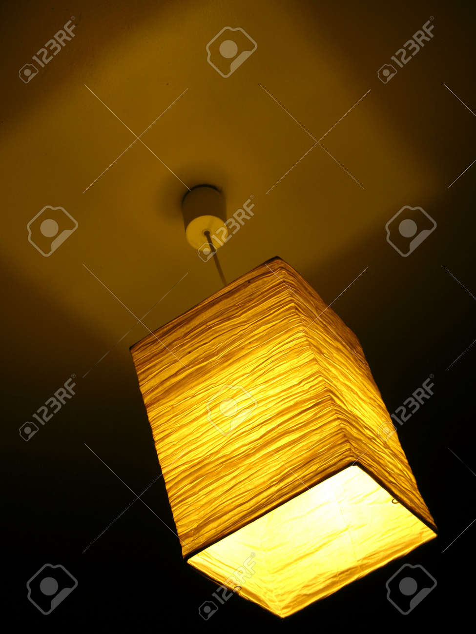 Overhead Lighting Overhead Light With Crinkled Cloth Lamp Shade Has A Golden Glow