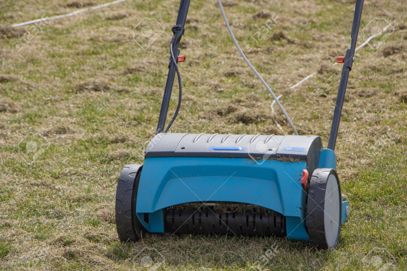 Grass Aerator Gardener Operating Soil Aeration Machine On Grass Lawn