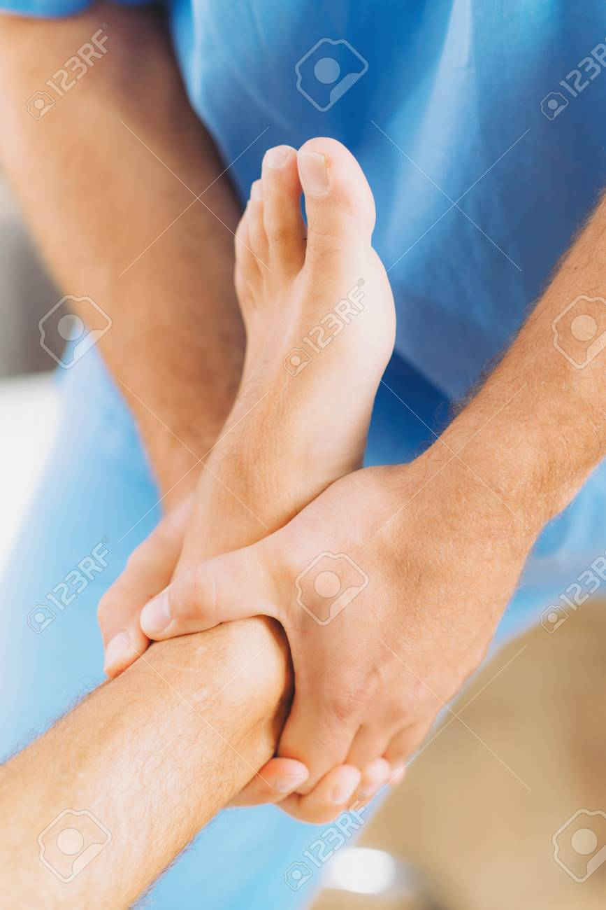 Healing Treatment Physiotherapist Doing Healing Treatment On Patient Foot Therapist