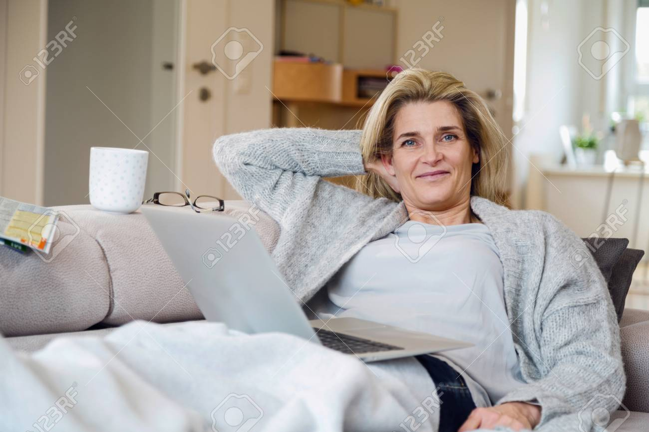 Sofa Magazin Portrait Of Relaxed Middle Aged Woman Sitting On Sofa At Home