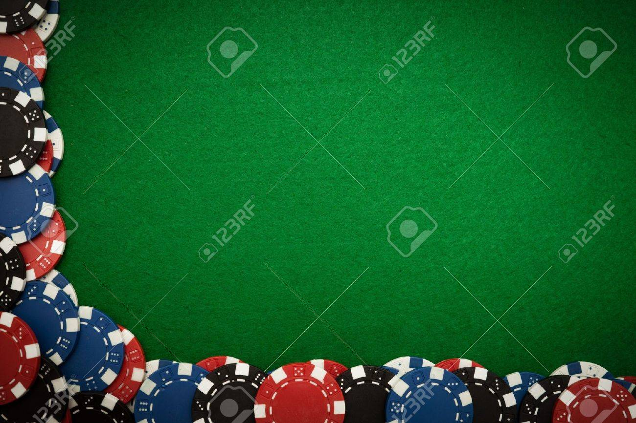 Poker table background colorful gambling chips on green felt background with copy space stock photo