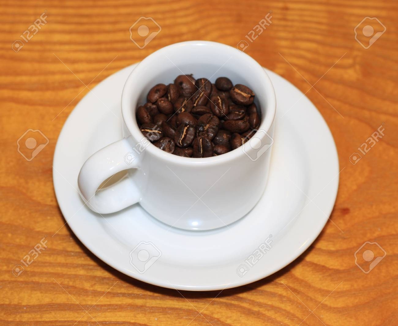 Small Coffee Cups And Saucers Small White Cup Of Roasted Coffee Beans With Saucer On A Wood