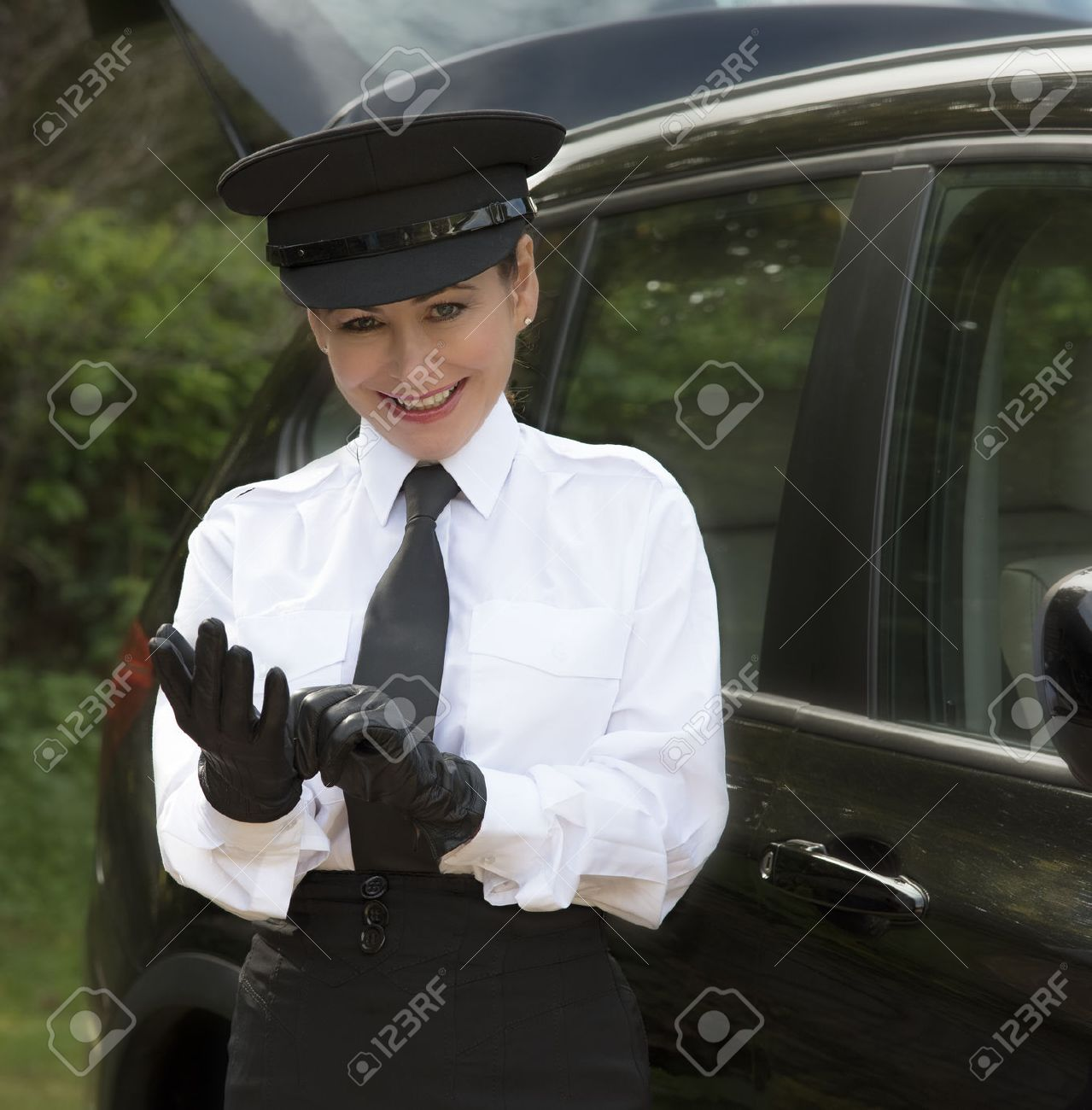 Stock photo woman chauffeur putting on her uniform black leather gloves
