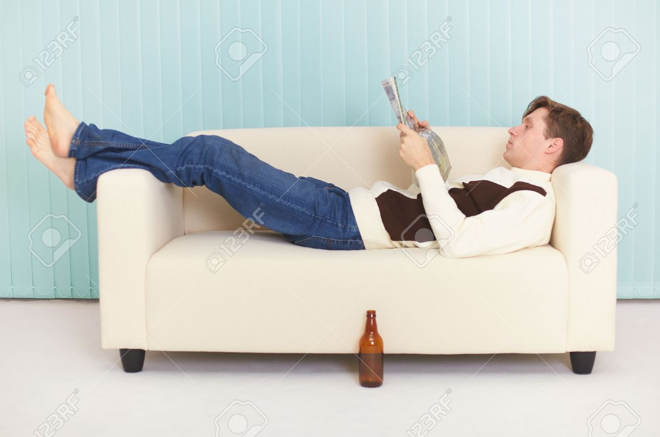 Sofa Magazin The Person Reads Magazine Comfortably Lying On A Sofa
