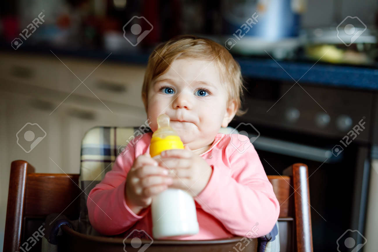 Nursing And Baby Biting Cute Adorable Baby Girl Holding Nursing Bottle And Drinking Formula