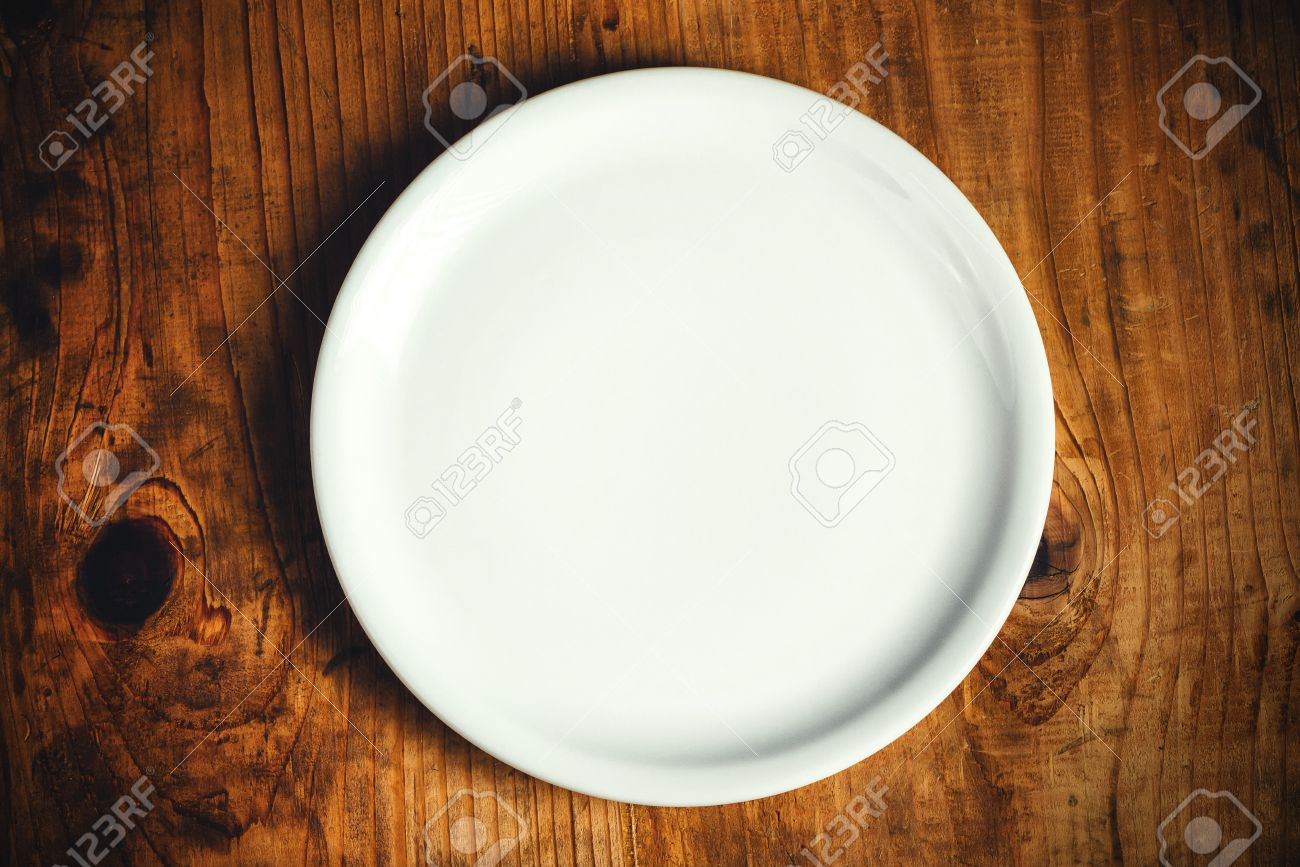 50260255 Empty white dinner plate on rustic wooden kitchen table top view Stock Photo