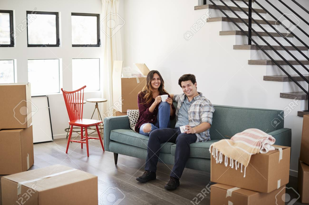 Home Sofa In A Box Portrait Of Happy Couple Resting On Sofa Surrounded By Boxes