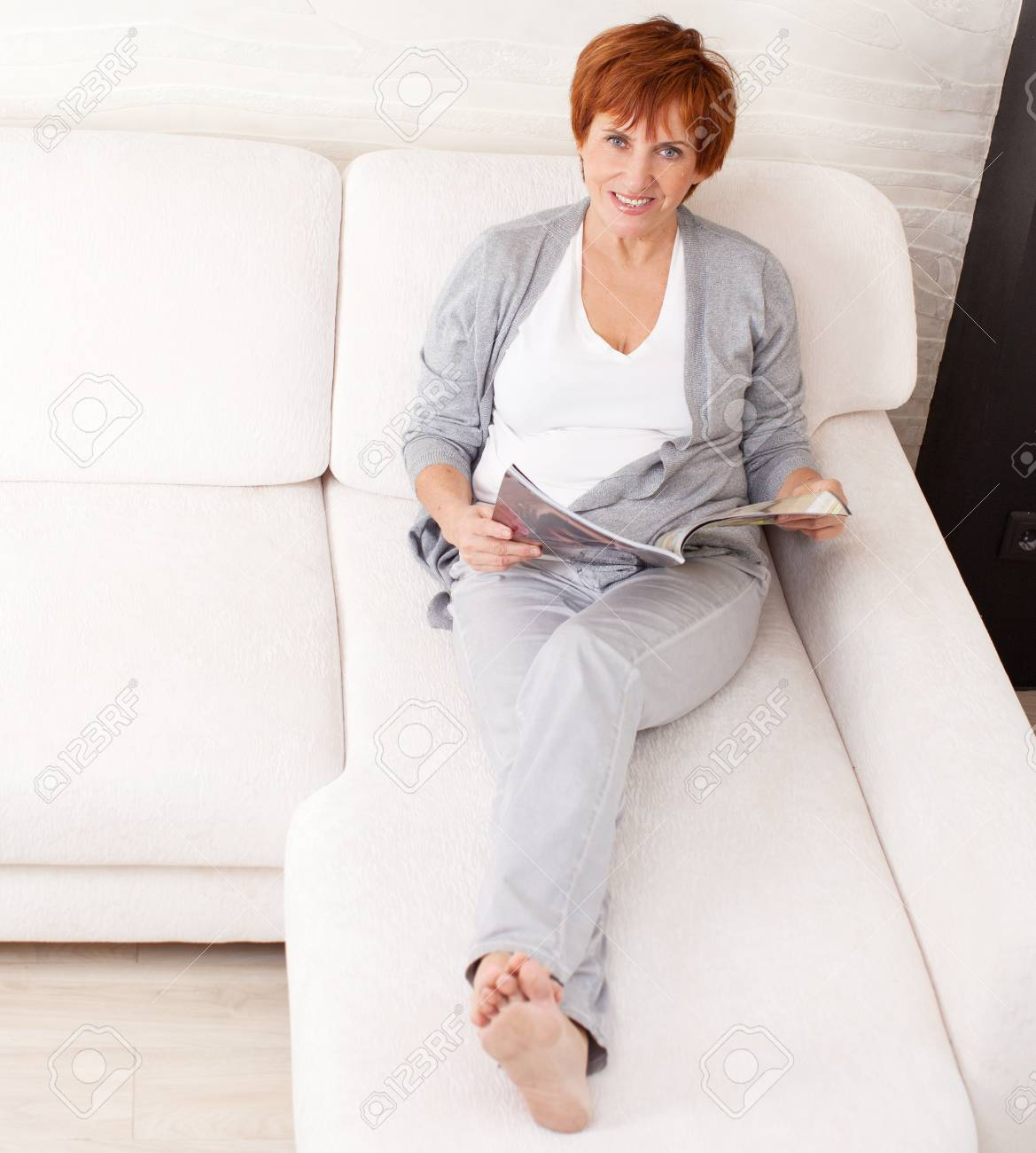 Couch Magazin Mature Woman Reading Magazin Lying At Sofa