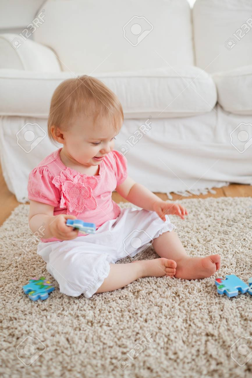 Tappeto Puzzle Baby Smile Baby Playing With Puzzle Pieces While Sitting On A Carpet In