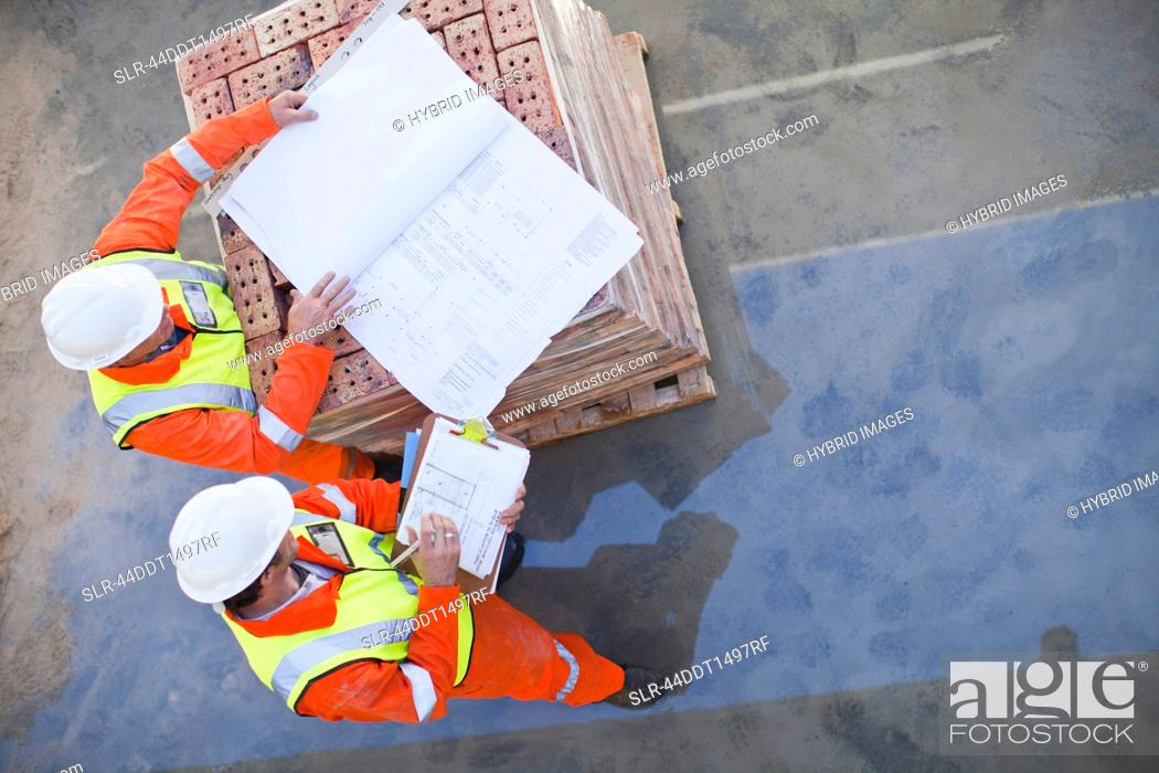 Workers reading blueprints on site, Stock Photo, Picture And Royalty