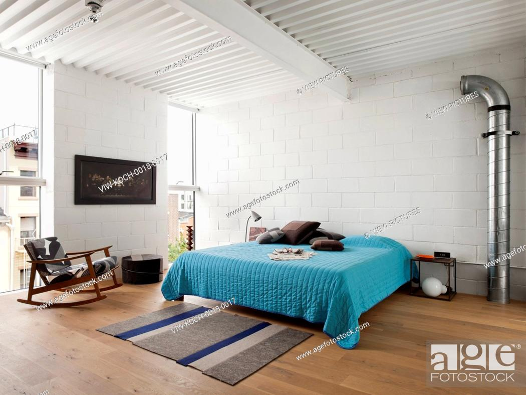Master bedroom with exposed CMU walls, white painted steel decking