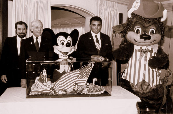 "Peter Paul, Buzz Aldrin, Mickey Mouse, Muhammad Ali, and Bisontennial Ben appear alongside a model of ""Communicating Freedom"", the California Bicentennial Foundation's float for the 1988 Tournament of Roses Parade."