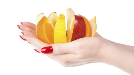 Woman hand with fruit mix. Isolated on white.
