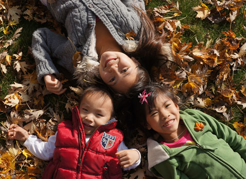 Pure Dental Family Kids laying in leaves