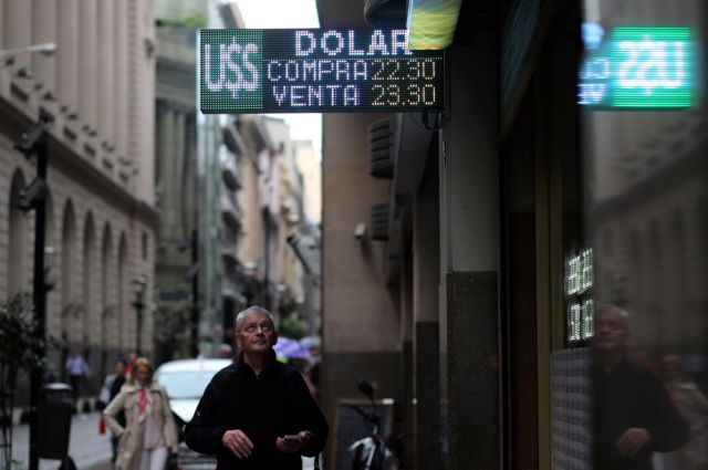 A man looks at an electronic board showing currency exchange rates in Buenos Aires' financial district, Argentina May 8, 2018. REUTERS/Marcos Brindicci