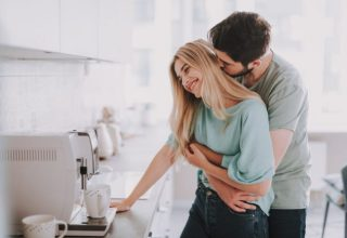 Bearded guy standing behind attractive blonde girl and kissing her. They are waiting for hot drink