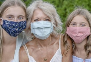 Close up of grandmother sitting with her two granddaughters wearing protective face masks to avoid the spread of COVID-19.