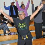 As she waits for her health screening, Patricia Williams of New Life Fellowship Church takes part in an impromptu workout session in the gymnasium at First Baptist Church-West. Both churches are part of the Village HeartBEAT program. (Photo: Qcitymetro.com
