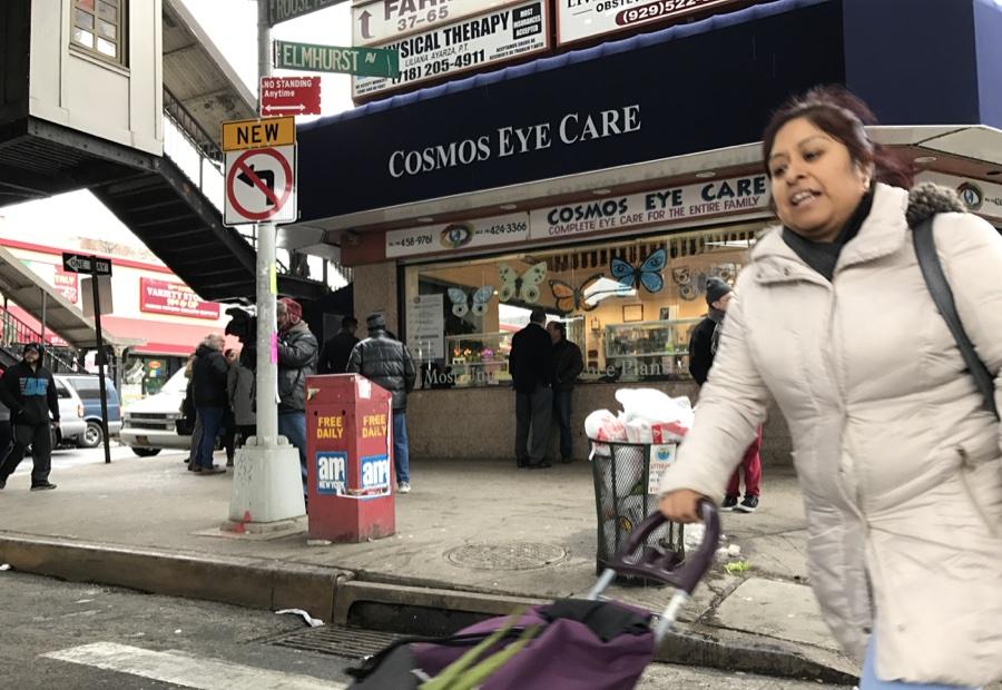 Una madre cruzando la Roosevelt al norte de la calle 90 en Jackson Heights, Queens.