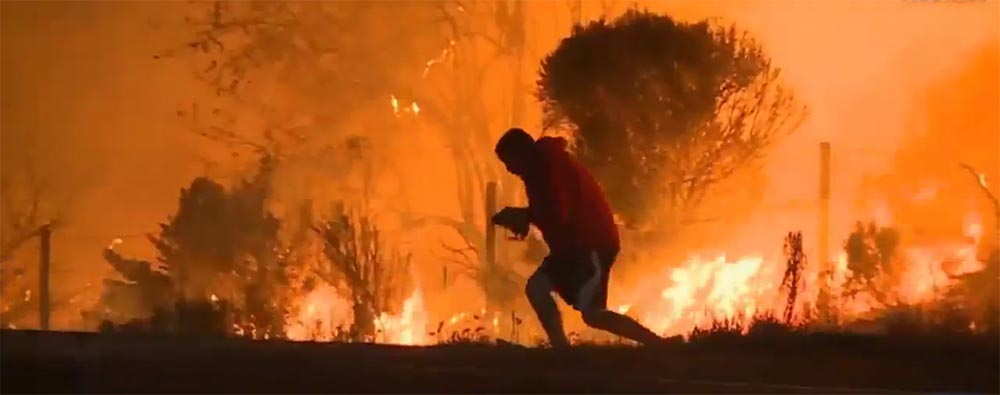 Un hombre retira un roedor de las llamas.
