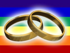 Two wedding rings shown against a rainbow flag