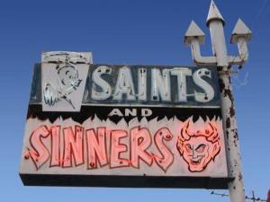 Fluorescent saints and sinners sign