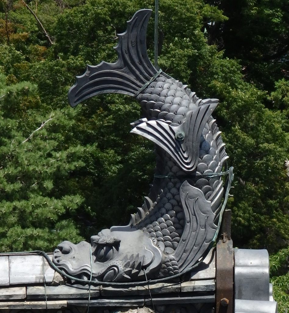 The form of a fish decorates each peak of the roof of Matsumoto Castle.