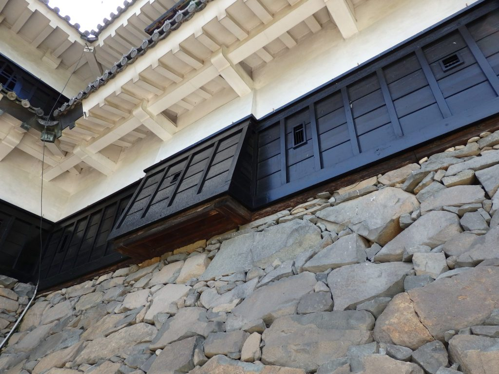 A piece of the wall extends out, allowing soldiers inside to drop stones on invading forces, at Matsumoto Castle.