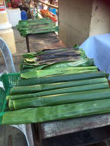 in Bananenblaetter gerollter sticky rice wird zum Verkauf angeboten