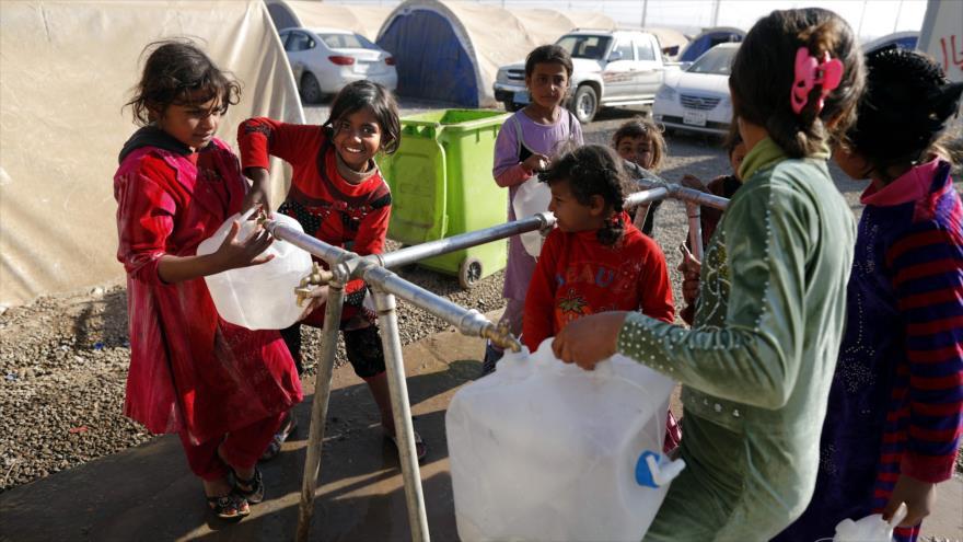 Niñas desplazadas iraquíes llenan sus contenedores de agua en el campo de refugiados Al-Khazar, cerca de Mosul (norte de Irak), 28 de noviembre de 2016.