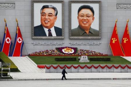 """El secretario de Estado estadounidense, Rex Tillerson, dijo que su país está buscando vías para presionar a Corea del Norte por su programa nuclear, al tiempo que un medio estatal norcoreano advirtió a Washington y dijo que """"no deberían meterse con nosotros"""". En la imagen, un hombre camina junto a imágenes del fundador de Corea del Norte Kim Il Sung y el líder Kim Jong Il en el centro de Pyongyang, el 16 de abril de  2017. REUTERS/Damir Sagolj"""