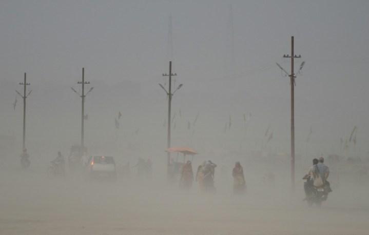Foto tomada el 16 de junio de 2017 muestra a peatones indios que caminan a través de una tormenta del polvo en el Sangam, la confluencia de los ríos Ganges, Yamuna y Saraswati, en Allahabad, India. AFP/Archivos / SANJAY KANOJIA
