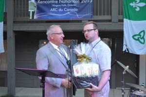 Denis Vaillancourt, président de l'Assemblée de la francophonie de l'Ontario, reçoit de M. Demers un panier-cadeau en remerciement de l'accueil en Ontario.