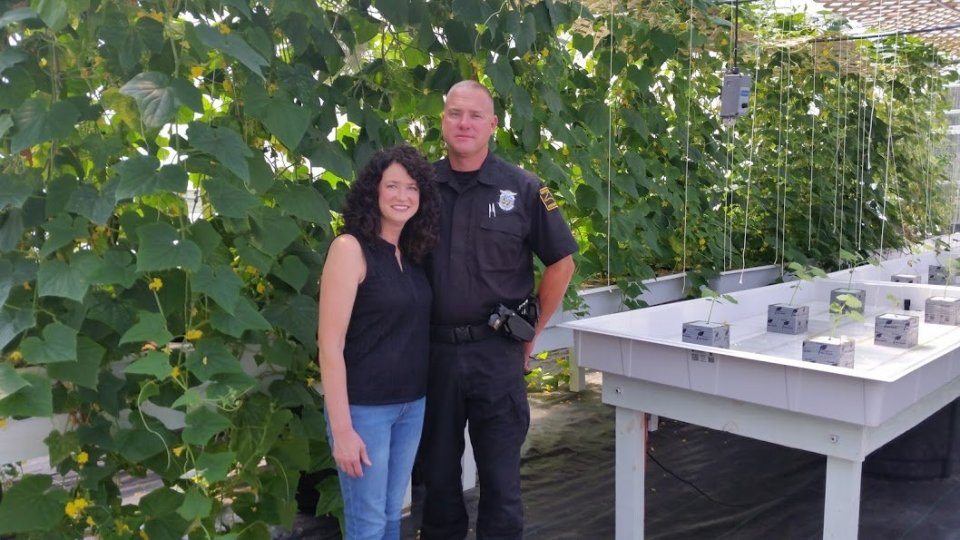 Wendy and Jeff Woolard in front of their climbing cucumbers. (Yes, Jeff is also an NC Highway Patrolman.)