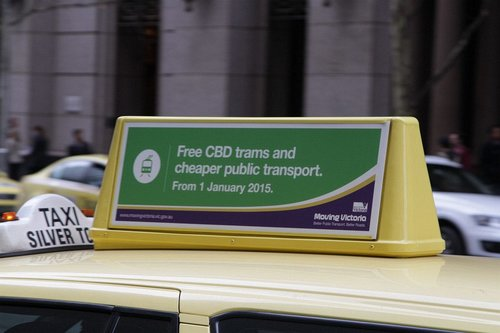 'Free CBD trams and cheaper public transport' propaganda atop a Melbourne taxi