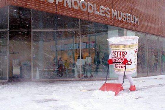Cup Noodle Mascot shoveling snow outside Cup Noodles Museum