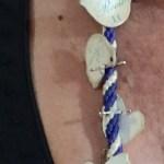 Cordón de medalla del Rocío con palomitas prendidas.
