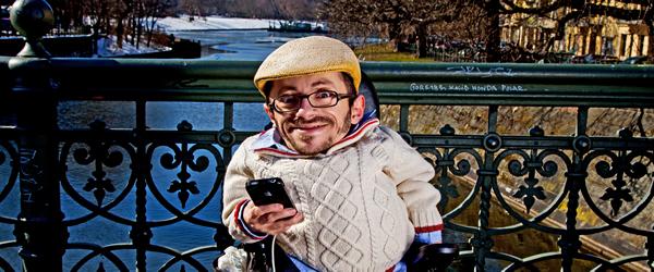 Raul steht mit einem Handy in der Hand auf einer Brücke.