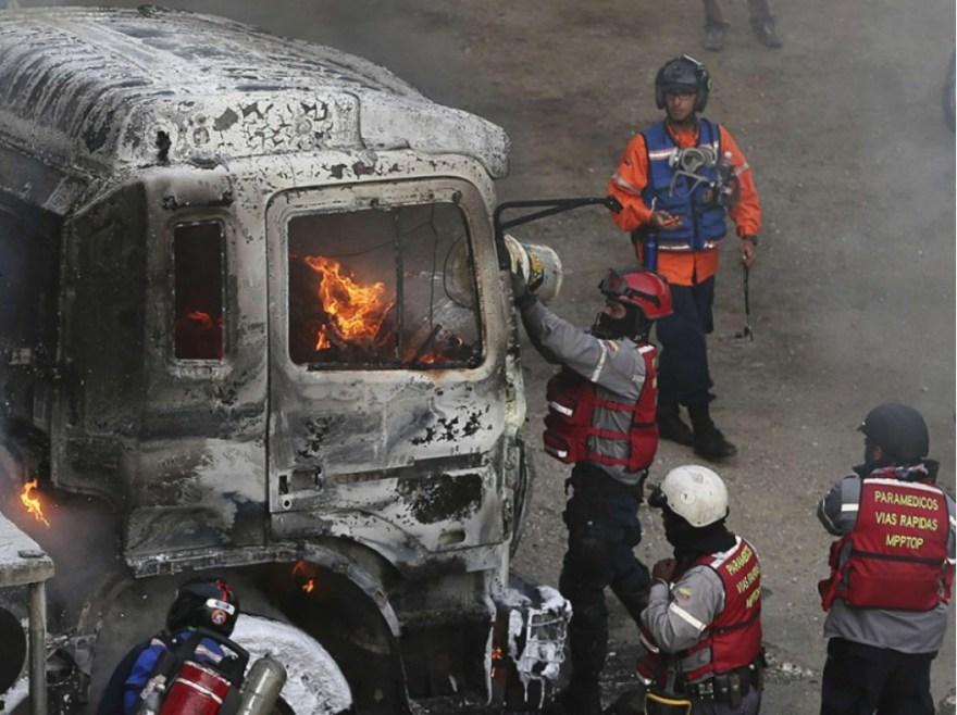 Des pompiers interviennent après qu'un bus a été enflammé par les manifestants.