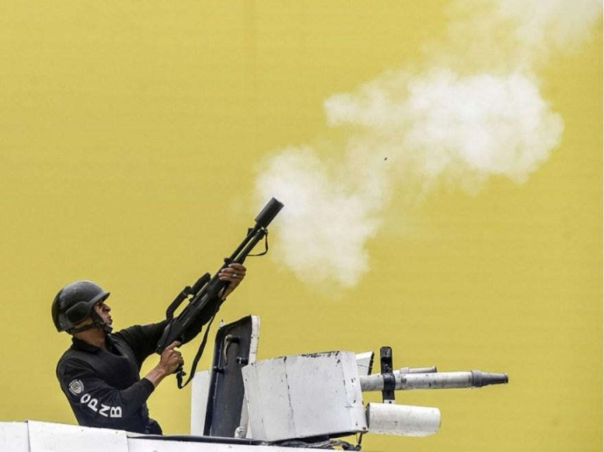 Un policier projette une grenade lacrymogène lors de la manifestation du 20 avril, à Caracas. Gouvernement et opposition s'accusent mutuellement des violences survenues depuis le début de la contestation.