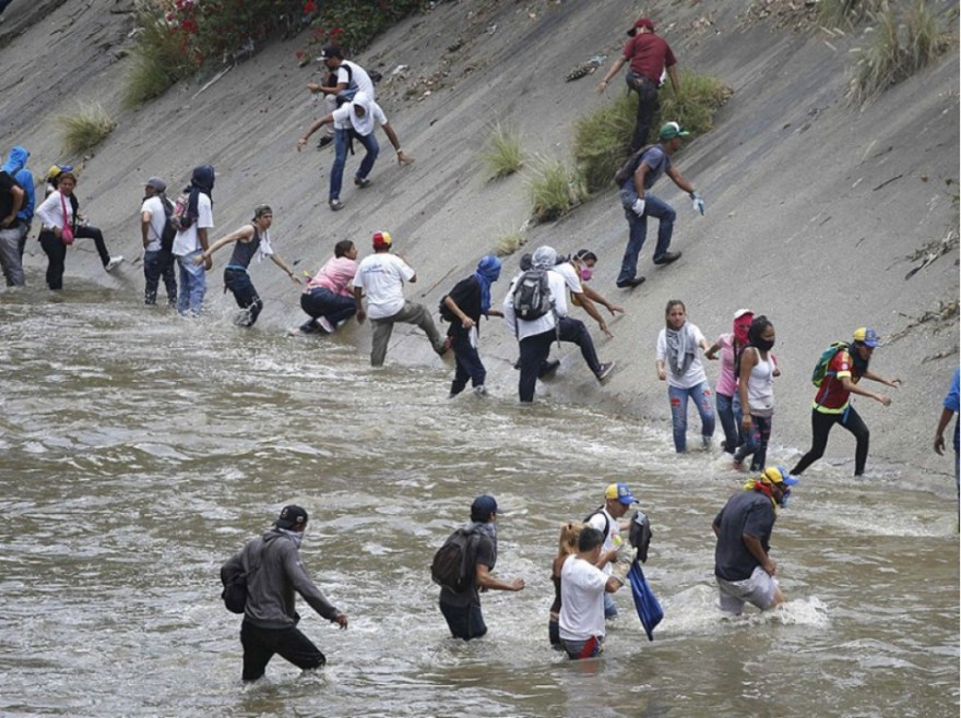 Des manifestants traversent la rivière Guaire pour échapper aux policiers, à Caracas, le 19 avril.