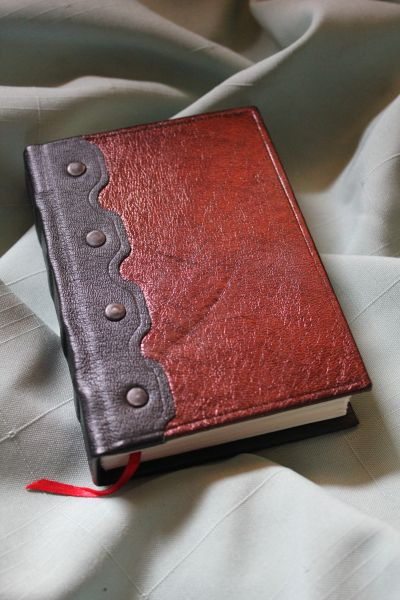 "This small journal is 3.5"" x 5"" and has a semi-rigid cover. It is wrapped with metallic burgundy lambskin & black pigskin."