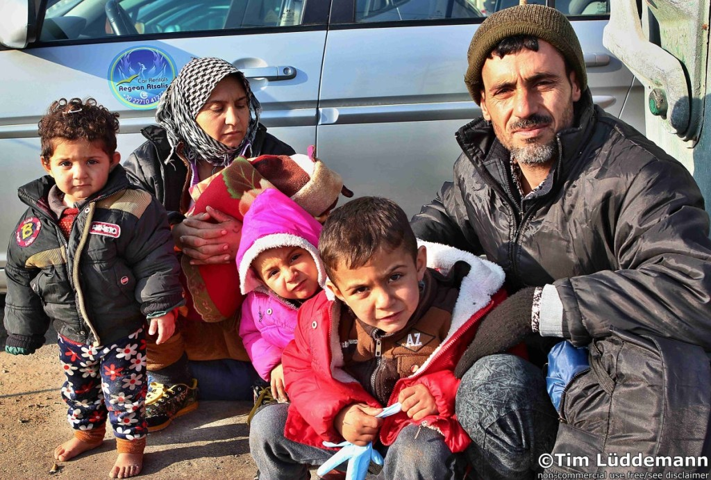 A Kurdish family waits after a dangerous boat trip on Chios on the onward journey