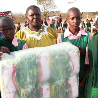 Nazi Kivutha, the wife of Makueni County governor Kivutha Kibwana standing with pupils of Kithathani Primary School after presenting them with free sanitary pads. [Picture:Nzinga Muasya ]