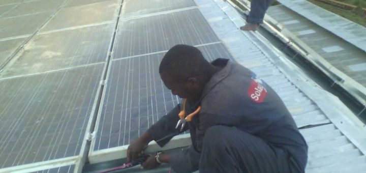 A solar installer fixing a solar panel on top of the roof at Kirwa's farm.Picture:Fred Deya
