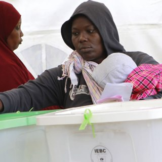A woman carries her baby as she votes.Many people shared babies in order to avoid  queues.Picture:Andrew Kilonzi